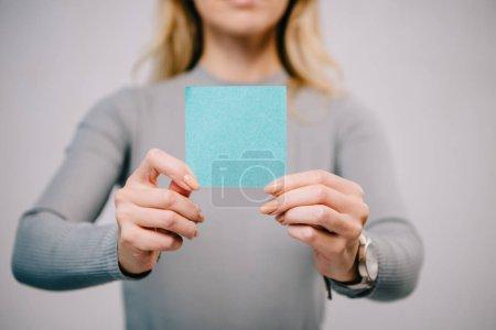 vue recadrée de femme tenant la note bleue papier vide isolé sur fond gris