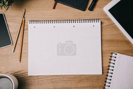 Photo pour Vue de dessus des fournitures, appareils numériques et bloc-notes vide en milieu de travail - image libre de droit