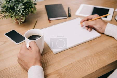 cropped view of businessman with cup of coffee writing in notebook at workplace with gadgets