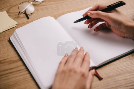 Photo for Cropped view of woman writing in notebook at workplace with glasses - Royalty Free Image