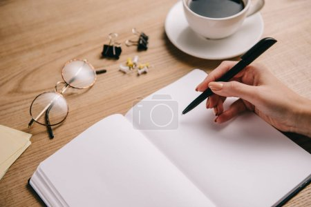 Photo for Partial view of woman writing in notebook at workplace with eyeglasses and cup of coffee - Royalty Free Image