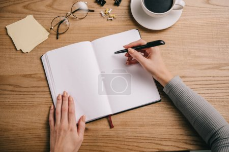 Photo for Cropped view of businesswoman writing in notebook at workplace with glasses and cup of coffee - Royalty Free Image