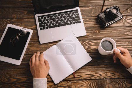 Photo for Cropped view of blogger with notebook, cup of coffee, digital devices and retro photo camera - Royalty Free Image