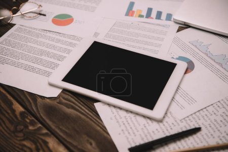 Photo for Digital tablet with blank screen and business documents on workplace - Royalty Free Image