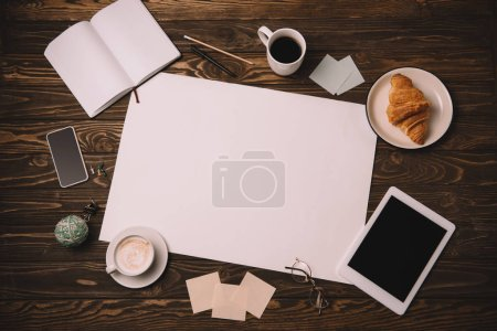 Photo for Top view of empty paper, business supplies, croissant and coffee cup on wooden table - Royalty Free Image