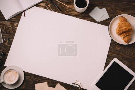 Photo pour Vue de dessus de papier vide, tablette numérique, fournitures, tasse de café et croissant sur la table en bois - image libre de droit