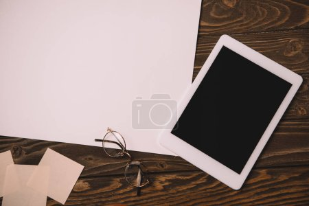 top view of digital tablet, eyeglasses and empty paper on wooden table