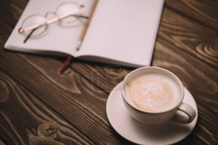 close up of cappuccino, notebook and eyeglasses on wooden table