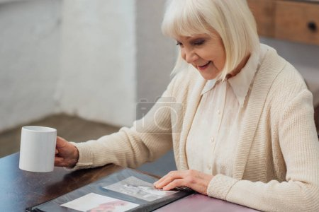 Foto de Mujer sonriente sentada en la mesa y mirando fotos mientras bebe café en casa - Imagen libre de derechos
