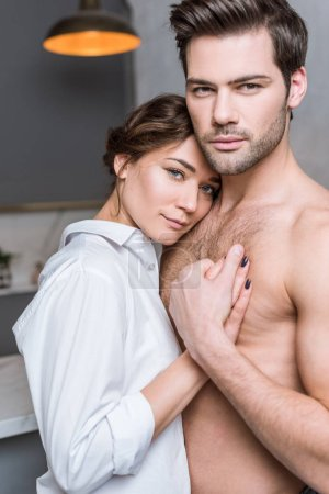 Adult tender couple embracing at home room kitchen