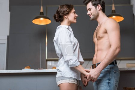 Adult tender couple looking into eyes while holding hands at home