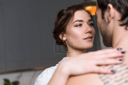 Beautiful tender girl looking into eyes and embracing boyfriend with tattoo