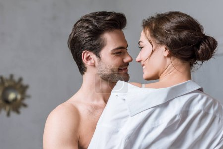adult man gently taking off shirt from girl and looking into eyes