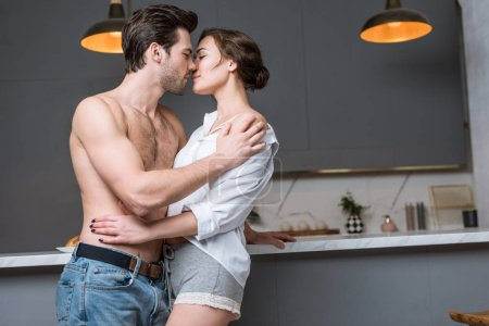 adult man and woman kissing at kitchen with closed eyes