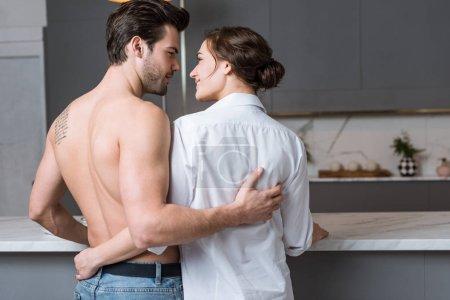 Photo pour Couple adulte embrassant et souriant à la maison - image libre de droit