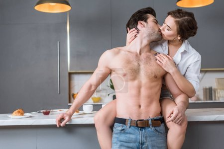 adult couple kissing at kitchen while woman sitting on tabletop