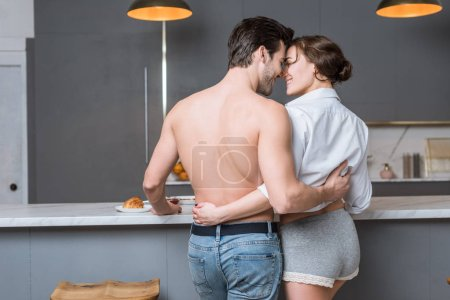back view of adult boyfriend and girlfriend embracing, looking into eyes and smiling at kitchen