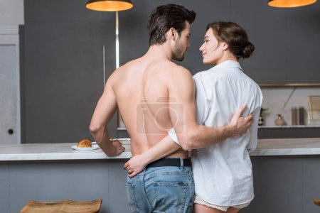 back view of adult couple embracing and smiling at kitchen