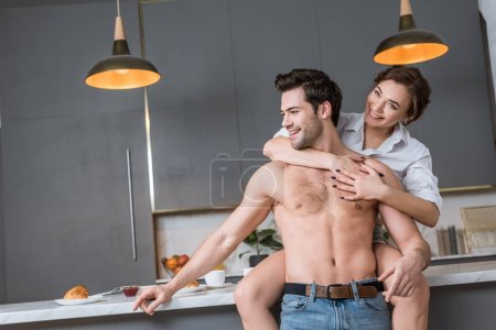 adult man and woman embracing and smiling at kitchen while woman looking at camera