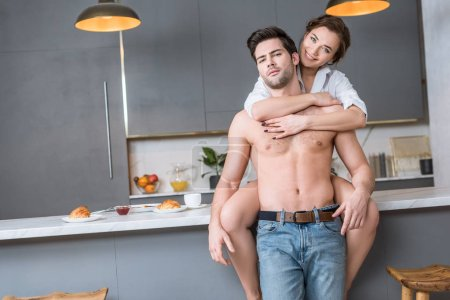 adult couple at kitchen embracing and looking at camera