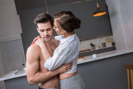 girlfriend hugging shirtless boyfriend while standing in kitchen