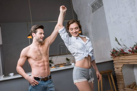 handsome shirtless man dancing with girlfriend at home