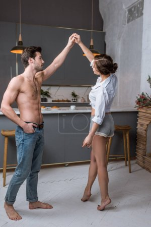 handsome man with hand in pocket dancing with girlfriend in kitchen