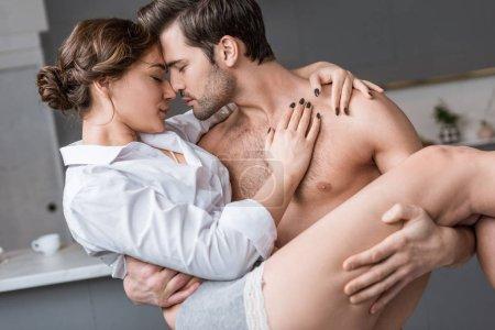 Photo pour Passionné homme torse nu tenant copine séduisante bras - image libre de droit