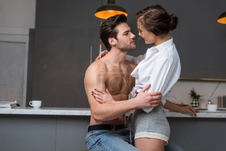 handsome shirtless man hugging and looking at girlfriend
