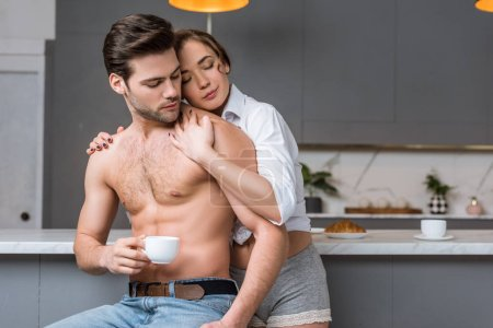 beautiful girlfriend embracing handsome shirtless boyfriend at home