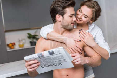 happy woman hugging handsome boyfriend with business newspaper in kitchen