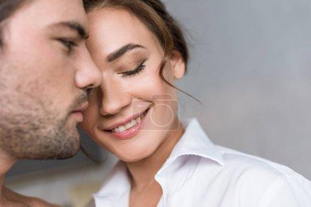 gros plan de jolie femme souriant avec des yeux fermés près de copain