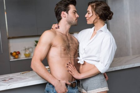 attractive girlfriend hugging passionate and shirtless boyfriend with hand in pocket