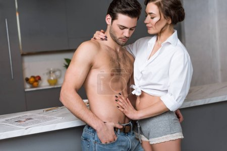 attractive woman looking at shirtless boyfriend with hand in pocket