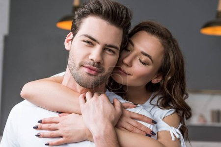 Photo pour Gros plan de jolie femme avec des yeux fermés embrassant homme - image libre de droit