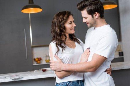 Photo pour Jolie femme étreignant et regardant beau petit ami dans la cuisine - image libre de droit