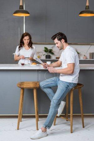 handsome man reading newspaper near beautiful girlfriend in kitchen
