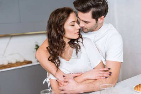 handsome boyfriend hugging  beautiful girlfriend in kitchen