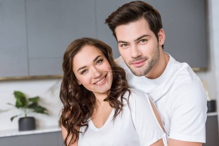 cheerful romantic couple smiling while looking at camera