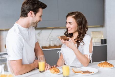 Photo for Attractive woman smiling while holding toast bread with chocolate near boyfriend - Royalty Free Image