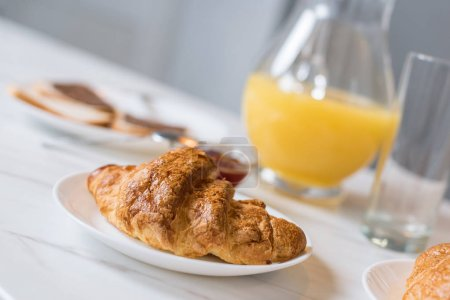 Photo for Selective focus of delicious croissant on plate with orange juice in jug on background - Royalty Free Image