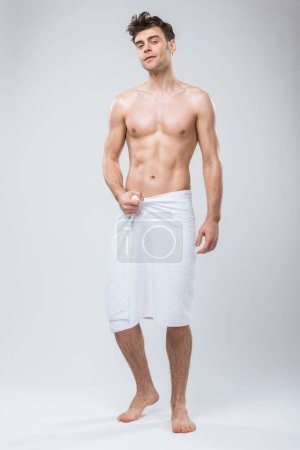 Photo for Handsome shirtless man posing in towel isolated on grey - Royalty Free Image
