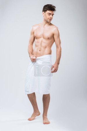Photo for Handsome muscular man posing in towel isolated on grey - Royalty Free Image