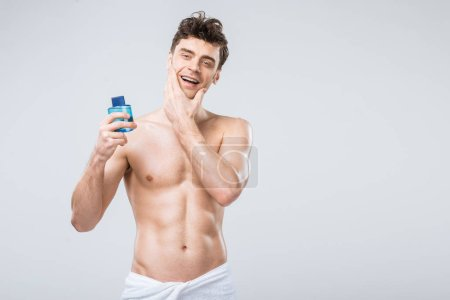 Photo for Happy shirtless man holding bottle with cologne, isolated on grey - Royalty Free Image