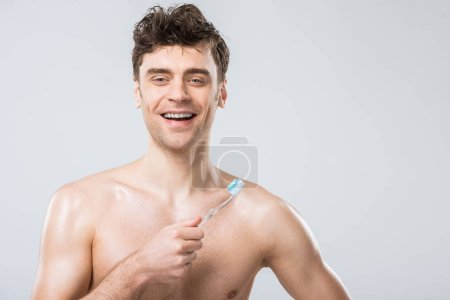 Photo for Handsome smiling man holding toothbrush with toothpaste, isolated on grey - Royalty Free Image