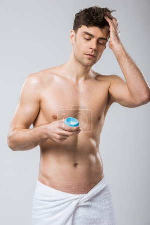 Photo for Handsome shirtless man applying hair styling gel, isolated on grey - Royalty Free Image