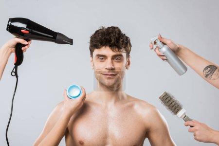 Foto de Manos de estilistas con spray, secador de pelo, peine y styling gel naer sonriente a hombre, aislado en gris - Imagen libre de derechos