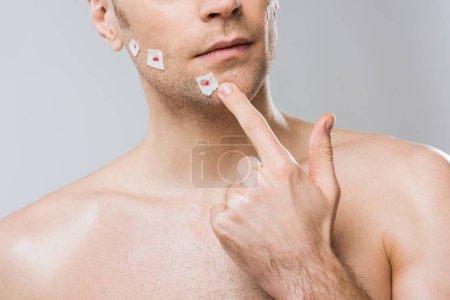 Photo pour Vue recadrée de l'homme touchant le visage après le rasage mauvais, isolé sur fond gris - image libre de droit