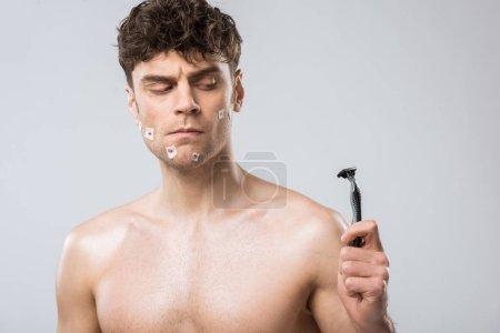 Photo pour Confondre homme regardant rasoir après le rasage mauvais, isolé sur fond gris - image libre de droit