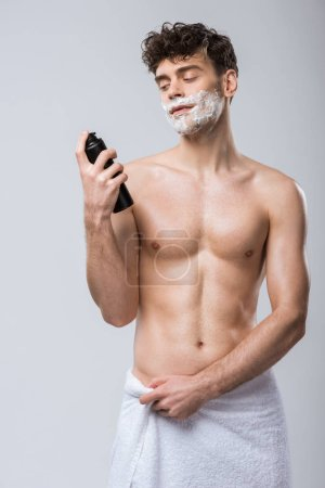Photo for Handsome young man in towel holding bottle with shaving foam, isolated on grey - Royalty Free Image